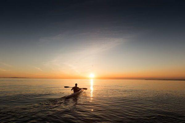Homme kayak de mer coucher de soleil